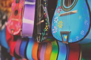 Разноцветни китари, окачени на стена - Музикална школа Sound Circle